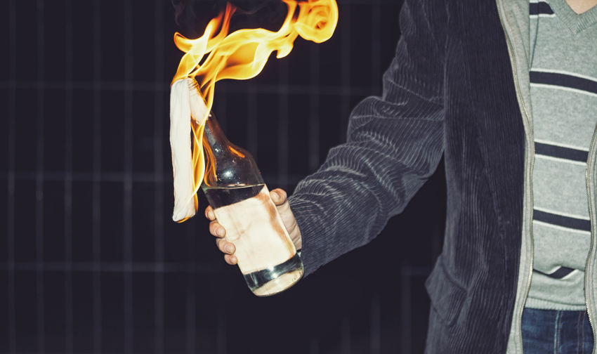 Midsection of man holding burning bottle against wall at night