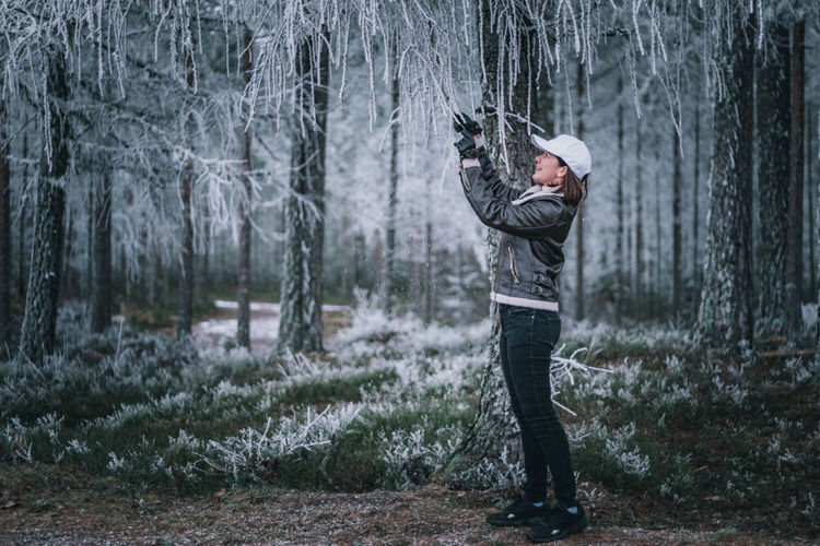 Woman standing by tree trunk in forest during winter