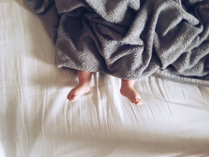 Low section of baby with blanket lying on bed