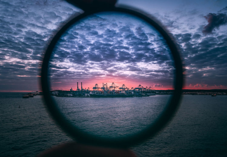 Commercial Dock Seen Through Ring Against Sky During Sunset