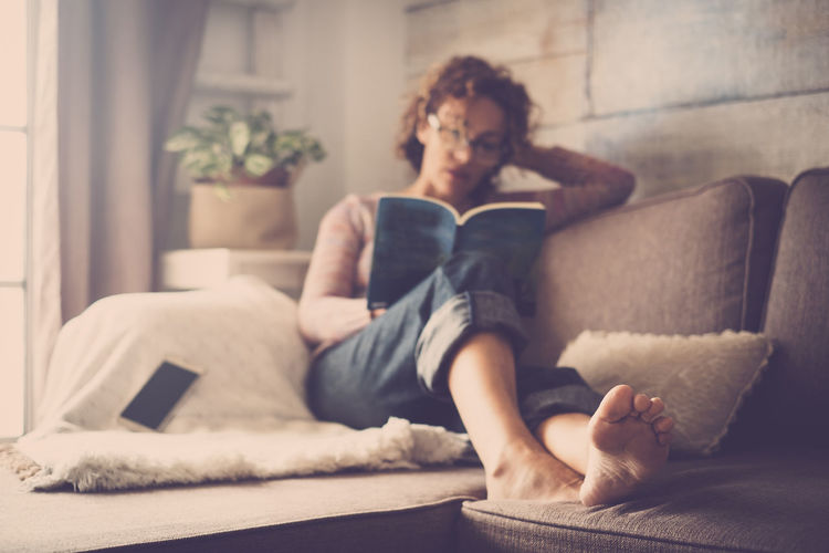 Young Woman Reading Book While Relaxing On Sofa At Home