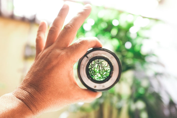 Cropped hand of person holding lens outdoors