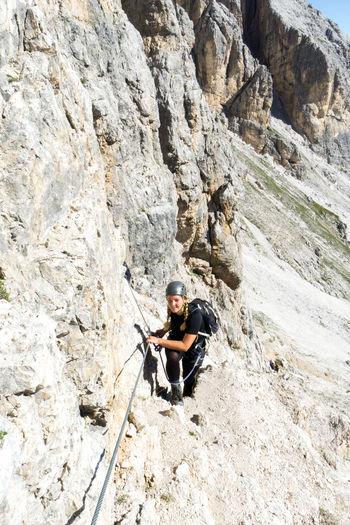 High angle view of woman climbing on mountain