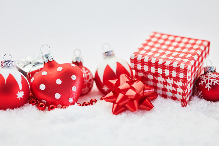 Close-up of red christmas baubles and gift boxes on snow