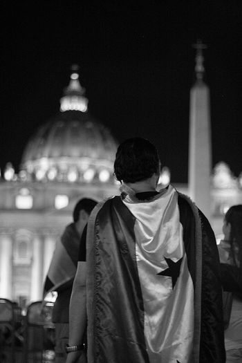 Rear View Of Man Wearing Cape Costume Standing Against St Peter Basilica