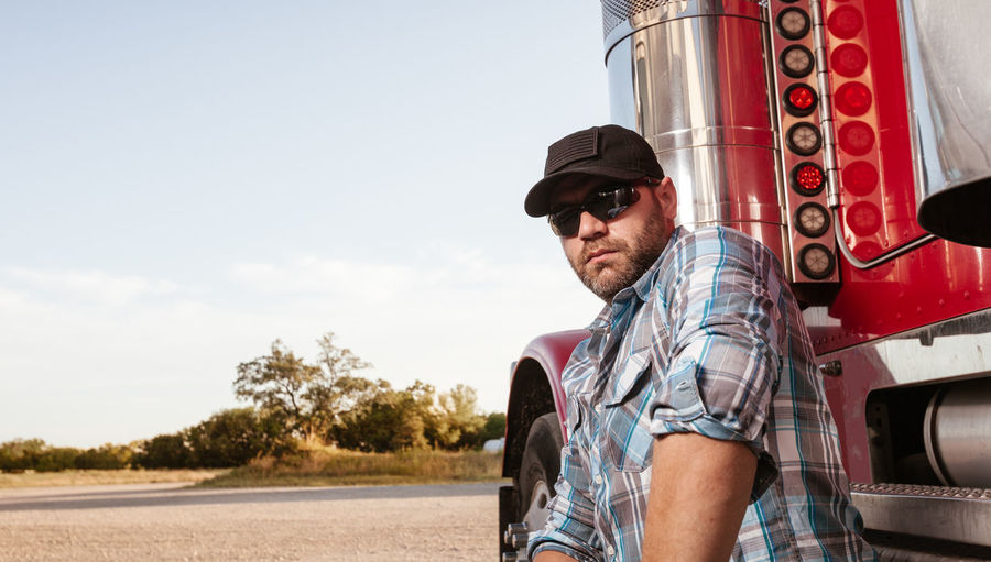 Portrait of man standing by truck outdoors