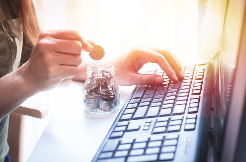 Midsection of woman with coin using computer