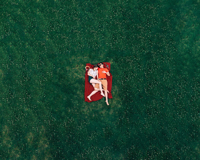 Aerial view of couple lying on textile over land