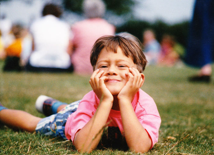 Portrait of boy with hand on chin lying on field at park