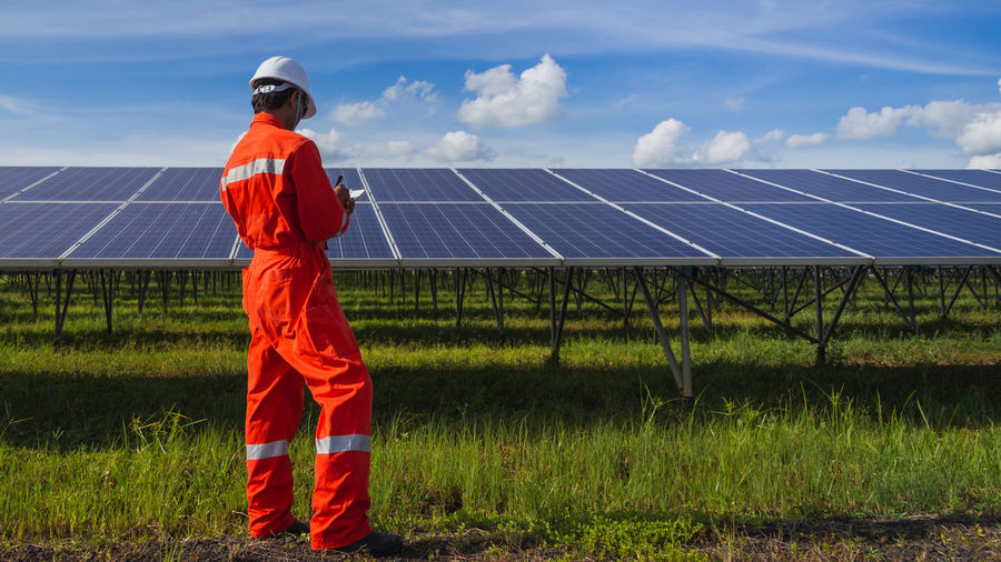 Rear view of man examining solar panels while standing on grassy field against blue sky