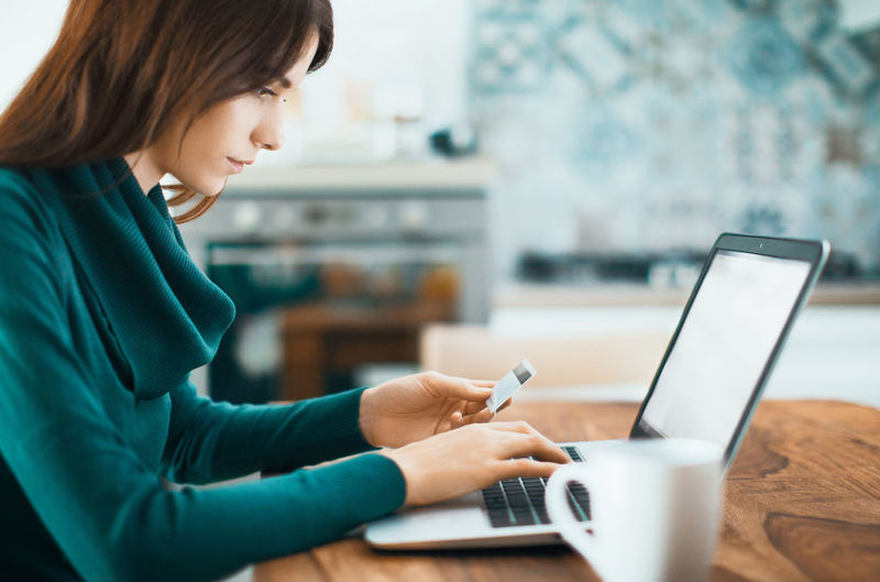 Young woman holding credit card while using laptop