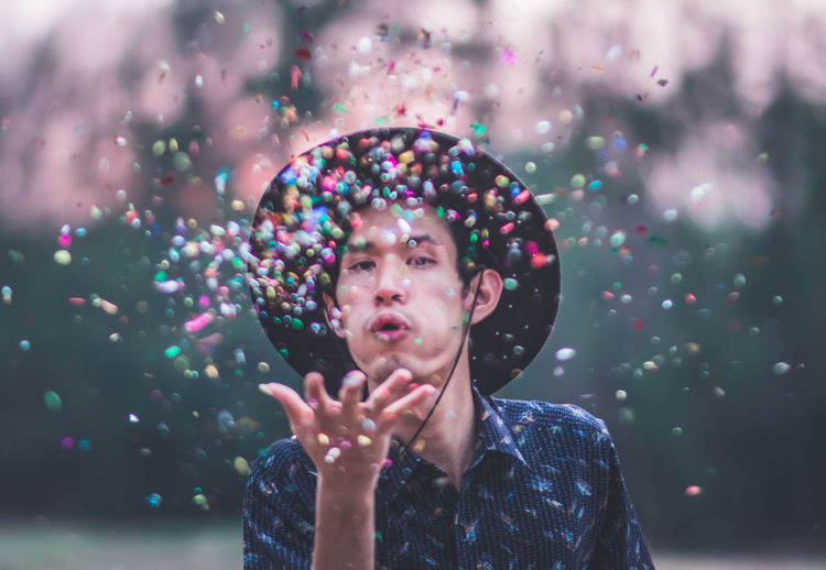 Portrait of young man blowing confetti