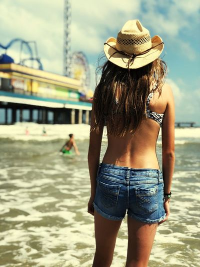 Rear view of woman in hat standing at beach
