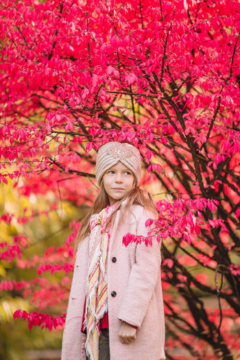 Portrait of woman standing against pink tree