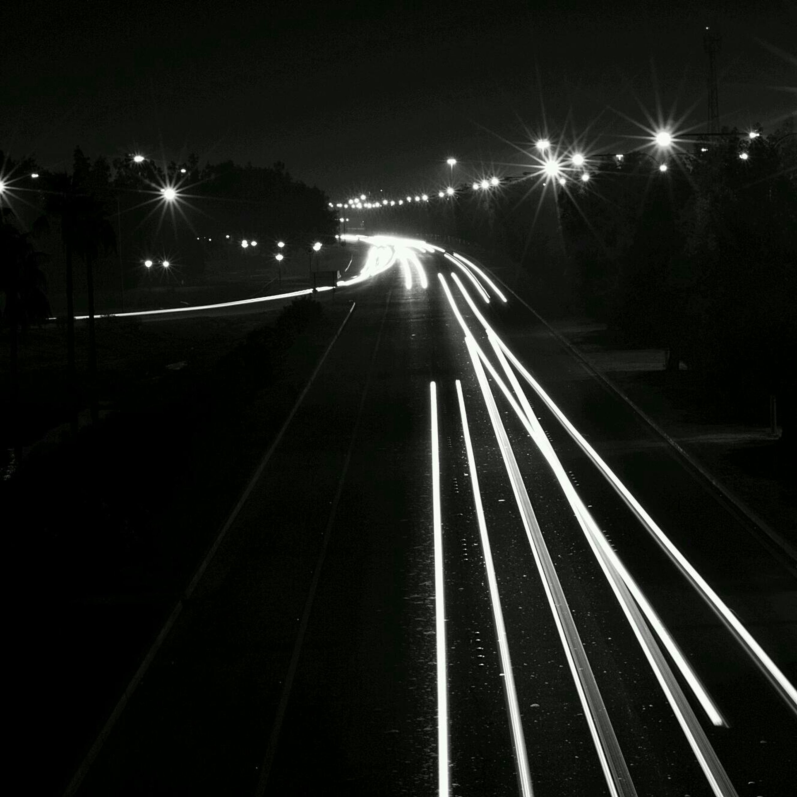 night, illuminated, transportation, the way forward, diminishing perspective, road, vanishing point, street light, road marking, light trail, lighting equipment, street, dark, high angle view, long, outdoors, empty, light - natural phenomenon, empty road, highway