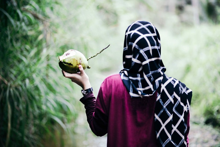 Rear view of woman holding coconut
