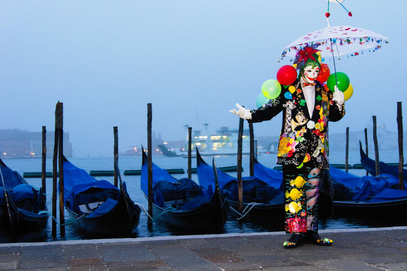 Carnival in Venice Carnival In Venice Balloons Clear Sky Clown Costume Day Gondola - Traditional Boat Mask - Disguise Men Nautical Vessel One Person Outdoors People Real People Sky Standing Water The Street Photographer - 2018 EyeEm Awards The Portraitist - 2018 EyeEm Awards The Photojournalist - 2018 EyeEm Awards