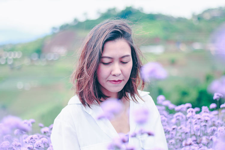 Portrait of beautiful woman with purple flower