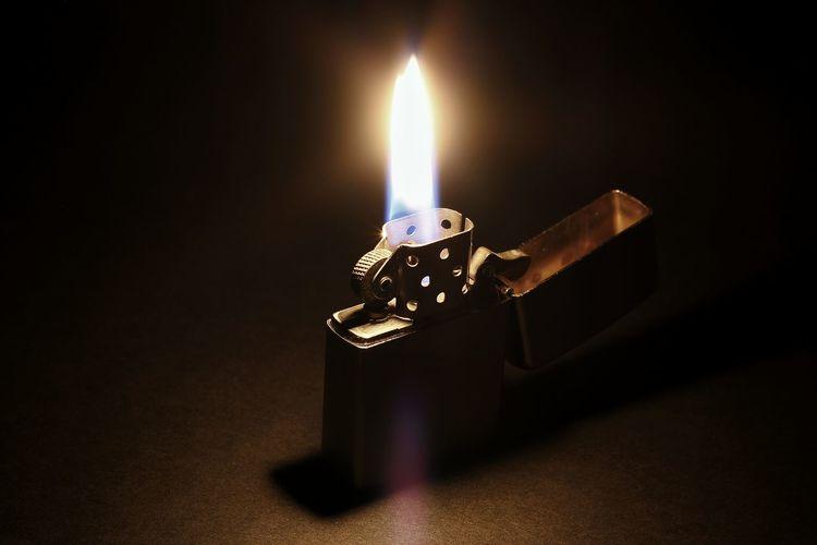 Close-up of lit cigarette lighter