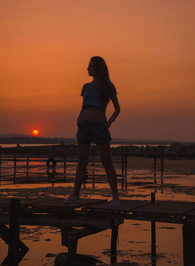 Silhouette mid adult woman standing at beach against orange sky during sunset
