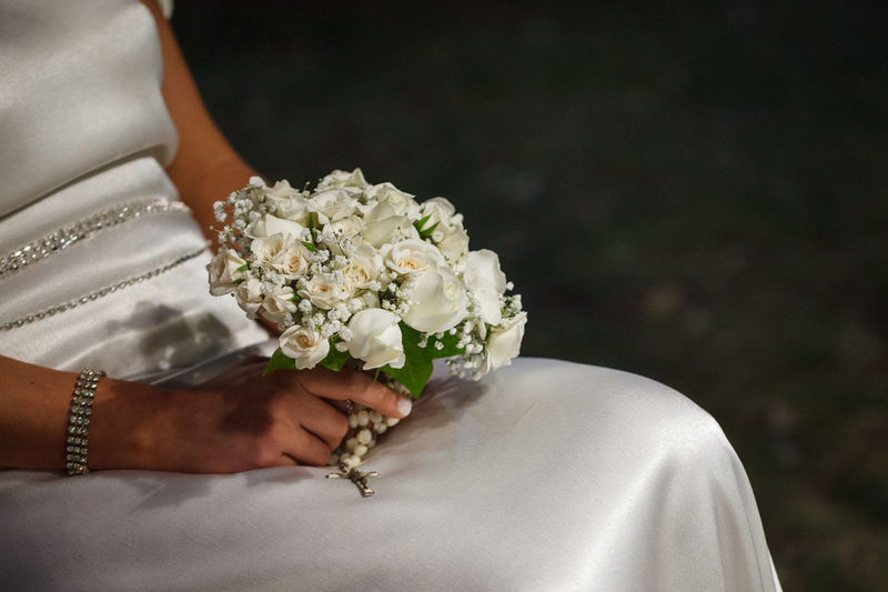 Midsection Of Bride Holding Bouquet And Rosary Beads At Wedding