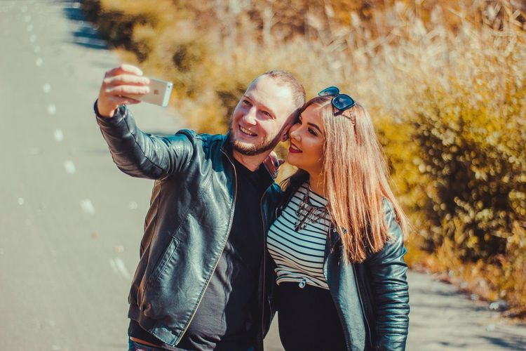 Happy couple taking selfie on road during sunny day