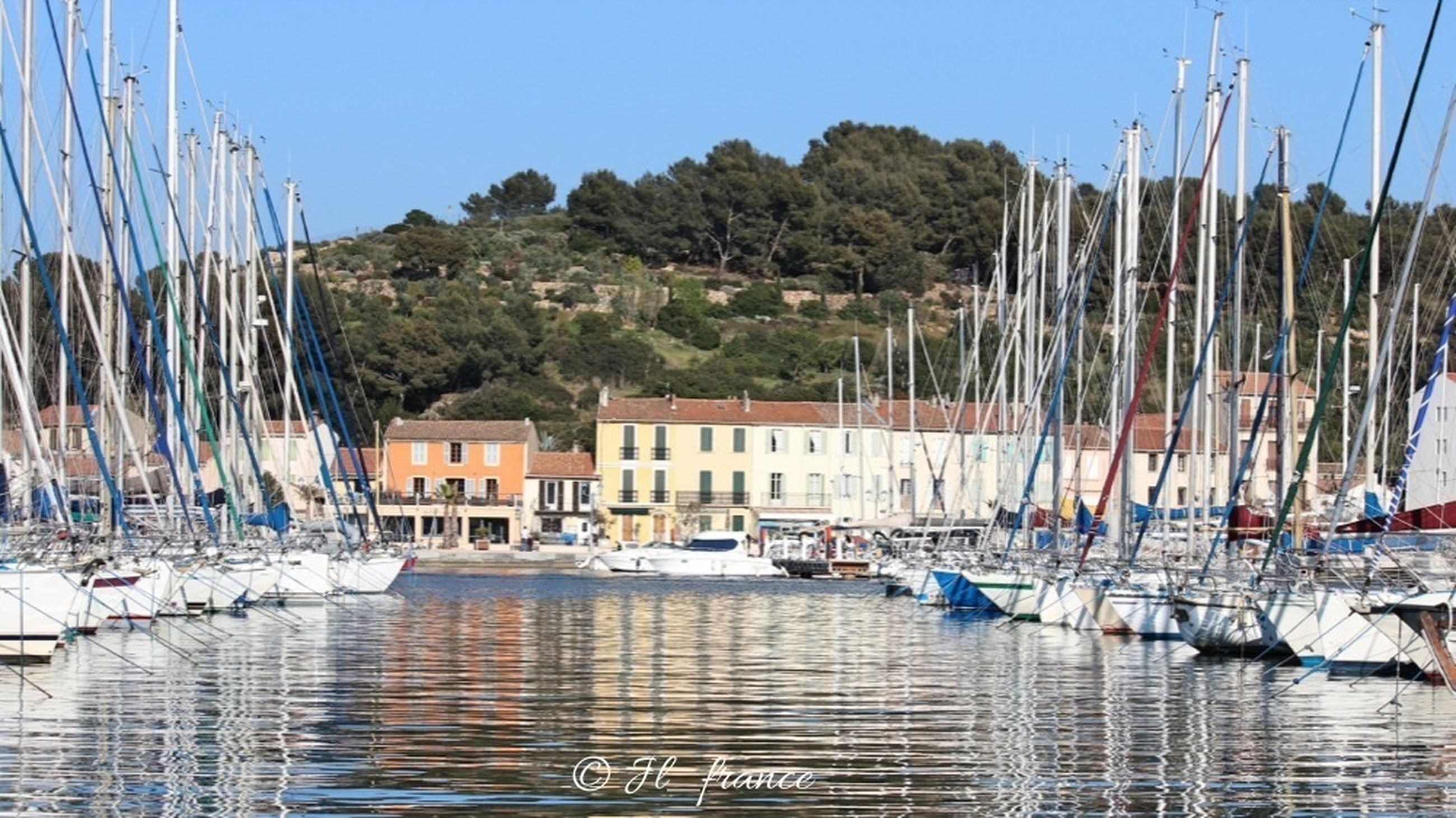 water, nautical vessel, moored, waterfront, harbor, transportation, blue, built structure, building exterior, architecture, boat, in a row, reflection, mode of transport, sea, panoramic, palm tree, mast, day, sailboat