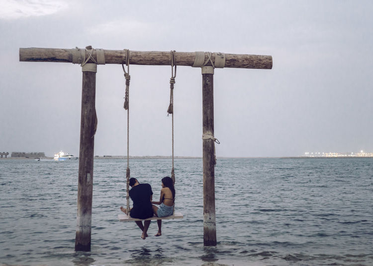 Rear view of couple sitting on rope swing over sea against sky