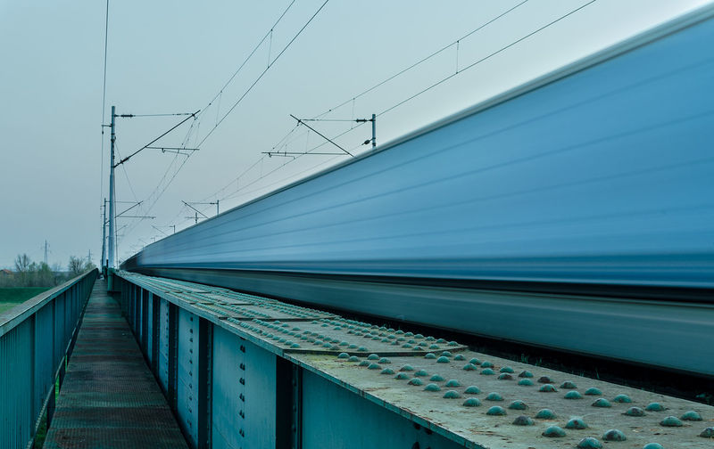 Blurred motion of train on railroad tracks against clear sky