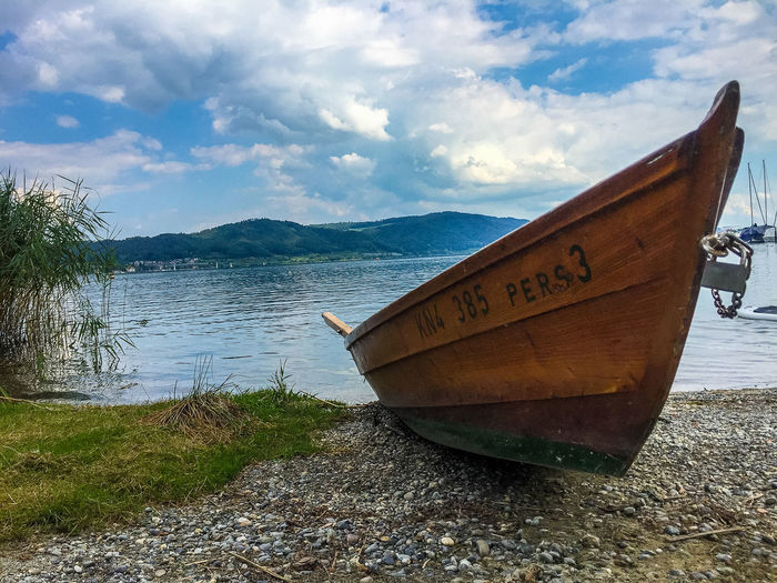 Sea Beach Water Nature Sky Day Outdoors Boat Tranquility Transportation Mountain Text Bodensee Scenics Beauty In Nature No People Mode Of Transport Moored Tranquil Scene Nautical Vessel Cloud - Sky EyeEmNewHere