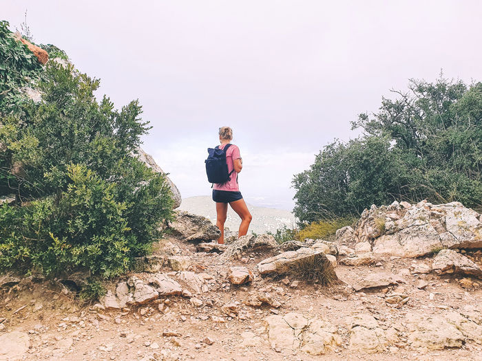 Female hiker standing next to the rock