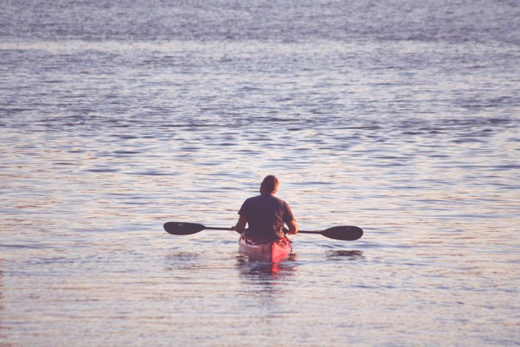 Rear View Of Man Kayaking In Sea