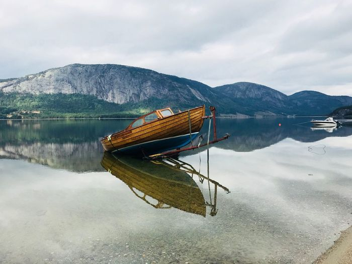 Boat moored on lake by mountains against cloudy sky