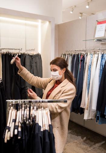 Woman wearing mask shopping at clothing store