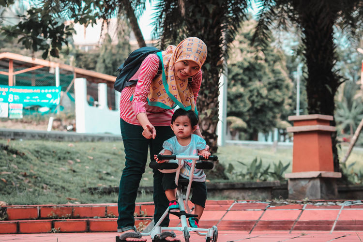 Portrait Of Smiling Woman With Daughter On Toy Scooter Playing In Park