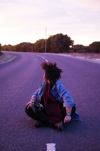 Man sitting on road against sky at sunset