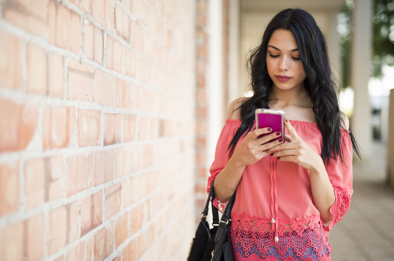Full length of woman holding mobile phone while standing against wall