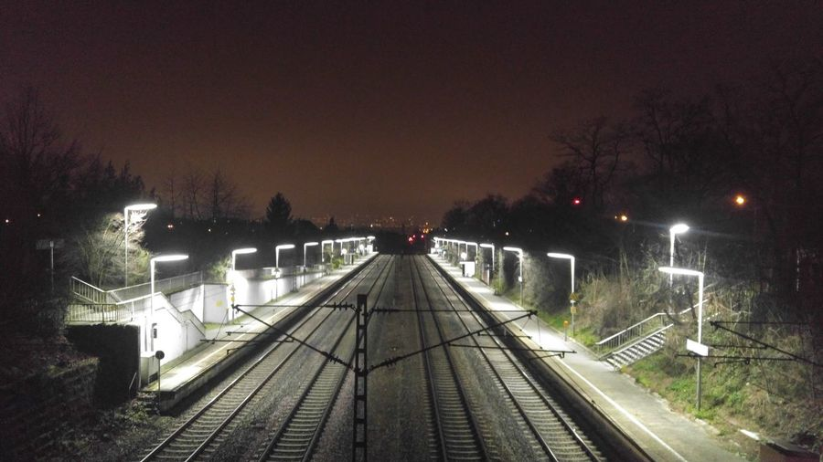 Railroad tracks against clear sky at night
