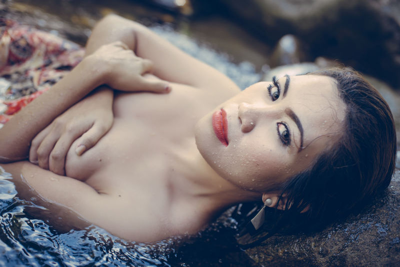 Close-up of beautiful woman lying in water