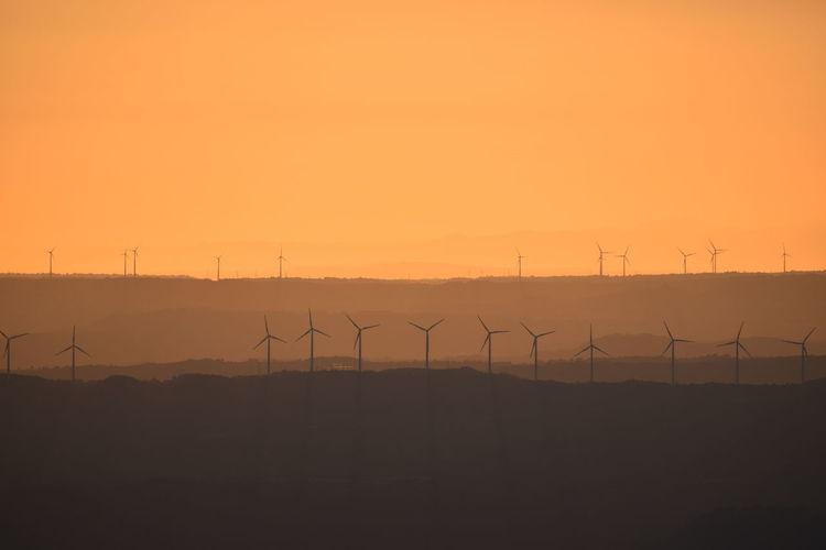 Silhouette wind turbines on land against orange sky