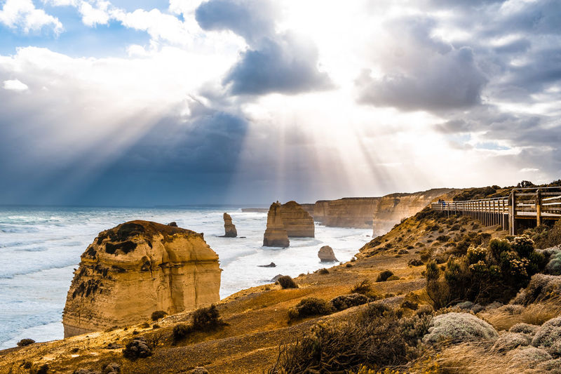 Sun rays through clouds shining on the twelve apostles rock formations on great ocean road