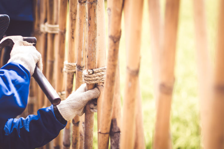 Midsection of man repairing wooden fence