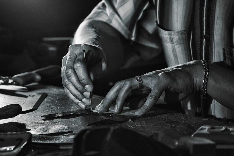The master of tanning works marks preparation Human Hand Workshop Real People Work Tool Human Body Part Selective Focus Midsection Craft Skill  One Person Indoors  Working Hand Finger Art And Craft Leather