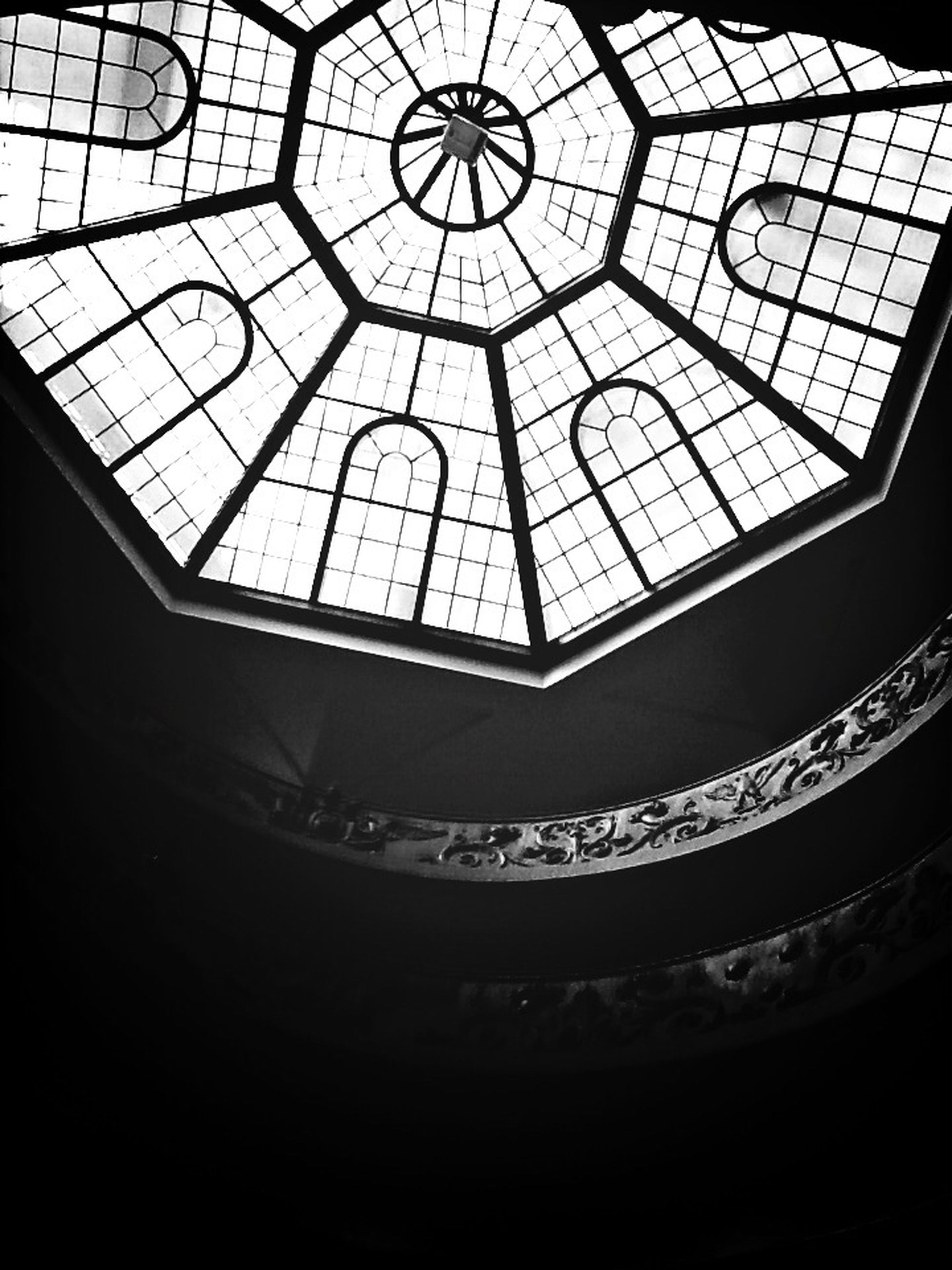 indoors, ceiling, low angle view, pattern, skylight, design, architecture, built structure, window, glass - material, directly below, architectural feature, geometric shape, silhouette, no people, interior, transparent, backgrounds, metal, illuminated