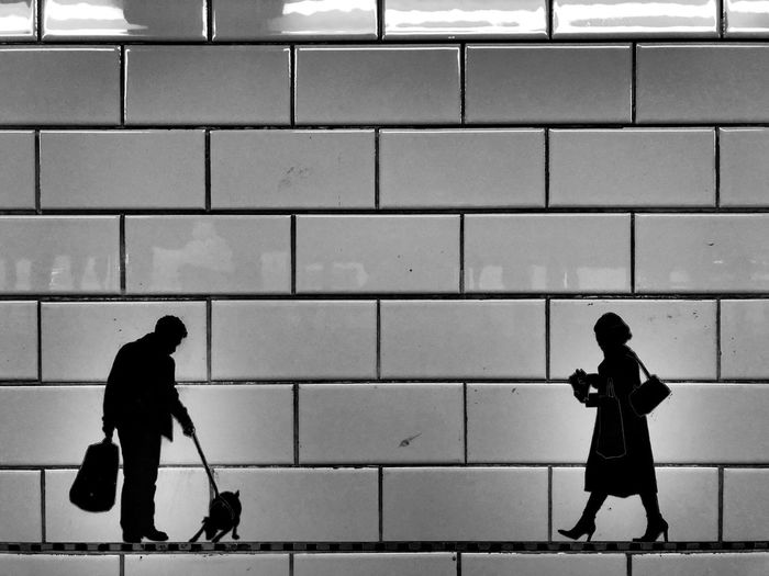 Side view of silhouette woman walking against wall