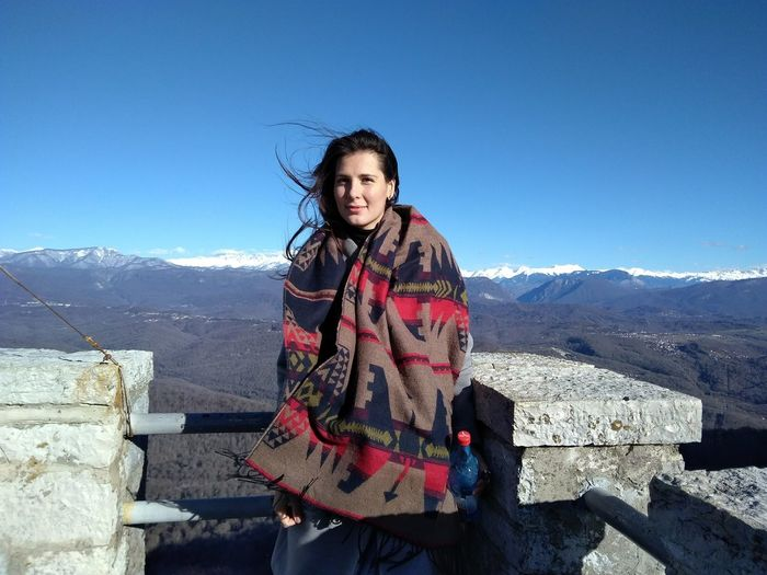 Portrait of smiling woman standing by railing against mountain