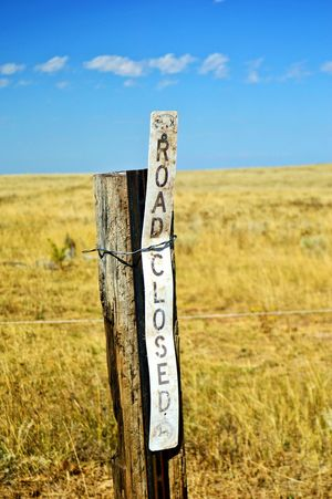 Closed to hunters vehicles Warning To Hunters Wood Material Plastic Material Sunshine North Of Lusk Wyoming Pasture Daylight Sign Letters And Words Wooden Post Field Sky Grass Landscape