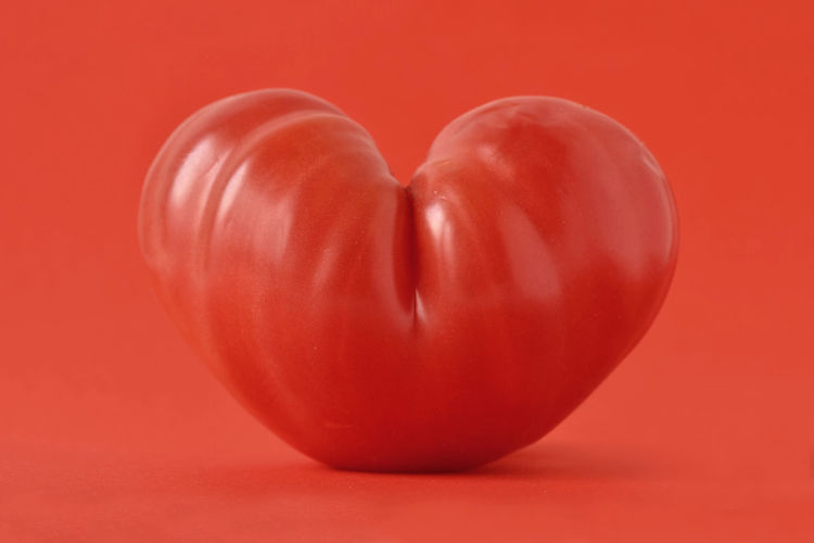 Heart shaped tomato on red background - Love concept Benefit Love Natural Red Shape Vegetarian Food Antioxidant Beef Heart Tomato Carotenoid Pigment Coeur De Beuf Concept Creative Food Health Healthy Heart Ideas Lycopene Nutrition Organic Symbol Tomato Vegan Vegetable Vitamin
