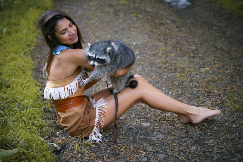 Young Woman In Traditional Clothing Playing With Raccoon In Forest