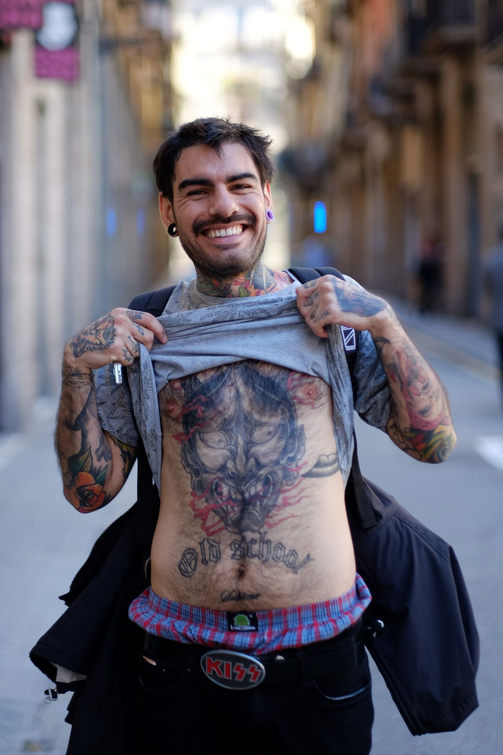 portrait, looking at camera, front view, one person, standing, tattoo, one man only, young adult, only men, adults only, fashion, smiling, people, city, happiness, adult, men, indoors, real people, shirtless, day
